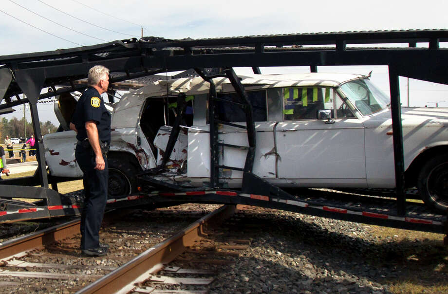 Investigators work the scene of a train accident on Brooks St. and U.S. 90, Monday, Jan. 7, 2013, in Sugarland. The driver of the truck was crossing the railroad tracks when its trailer got stuck on the tracks. The driver was not able to get off the tracks in time. Photo: Cody Duty, Houston Chronicle / © 2012 Houston Chronicle