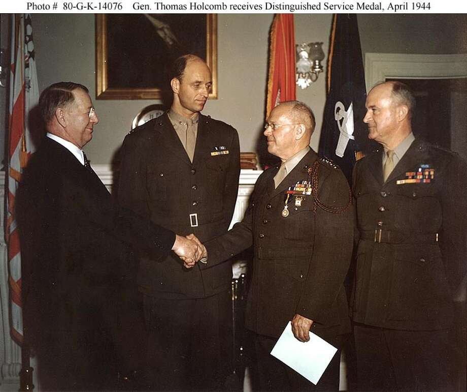 Receives the congratulations of Secretary of the Navy Frank Knox, upon being presented with the Distinguished Service Medal in recognition of his service as Commandant of the Marine Corps from 1 December 1936 to 1 January 1944. The presentation took place in Secretary Knox' office on 12 April 1944. Looking on are Lieutenant General Alexander A. Vandegrift, Commandant of the Marine Corps (right) and Colonel James Roosevelt. (National Archives / Official U.S. Navy Photograph)