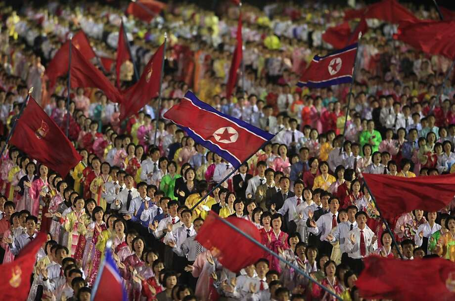 Students wave the national flag at a celebration honoring the late founder's 100th birthday in April. Photo: Ng Han Guan, Associated Press
