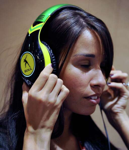 Shauna Cyr wears a pair of USD 299 Soul SL300 noise-cancelling headphonesduring a 2013 Consumer Elec