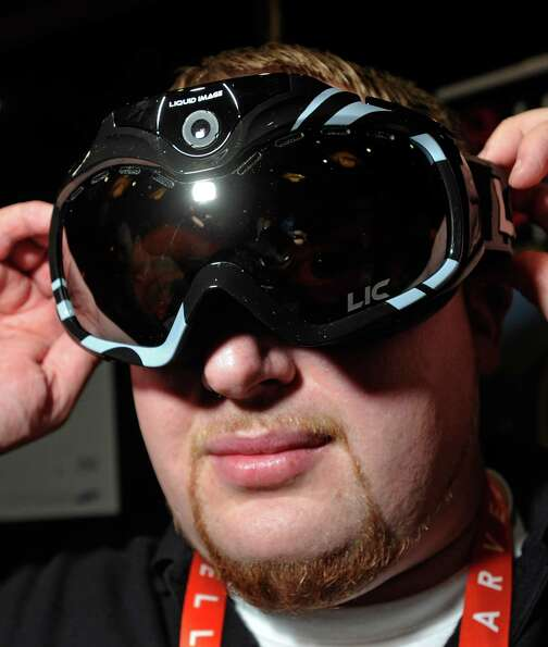 John Noonan displays a pair of Liquid Image goggles with a built in camera during a 2013 Consumer El
