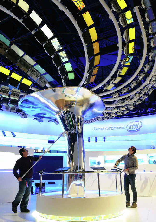 workers position 176 Windows 8 Ultrabook devices on a massive tree within Intel's cornerstone booth for the International Consumer Electronics Show, Saturday, Jan. 5, 2013, inside the Convention Center in Las Vegas. Photo: AP