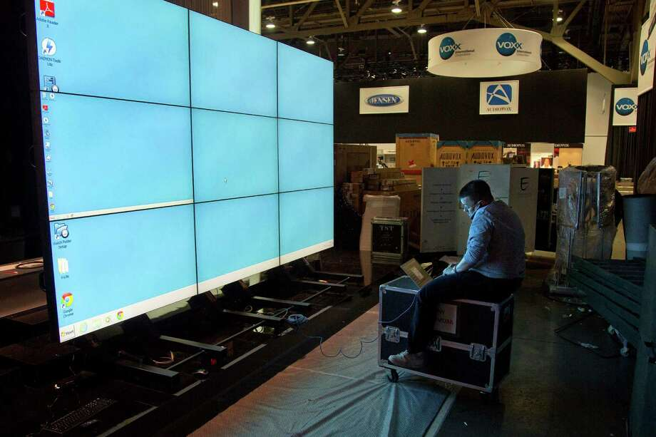 Sharp Electronics employee Michael Nenortas programs a flat-screen display at the company's booth for the International Consumer Electronics Show on Jan. 6, 2013, in Las Vegas. Photo: AP