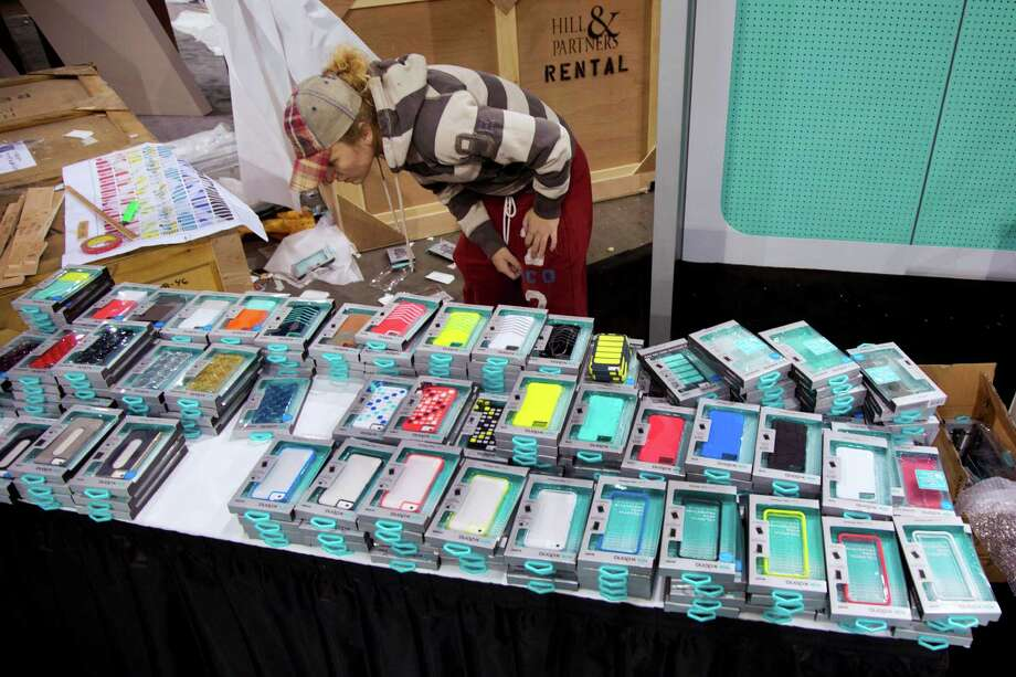 Las Vegas Convention Center exhibit contractor Ruachelle Kulak searches through stacks of cell phone cases while setting up a booth for X-Doria on Jan. 6, 2013, in Las Vegas. Photo: AP