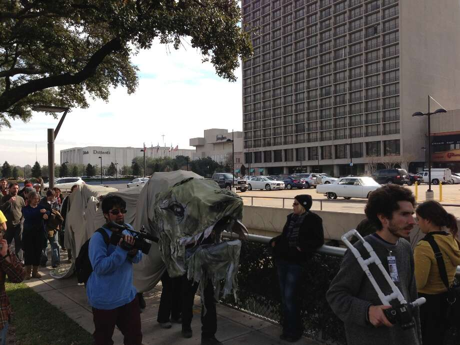 Protesters, costumed as a papier-mache dragon, march near Houston's Galleria mall to oppose the Keystone XL Pipeline.