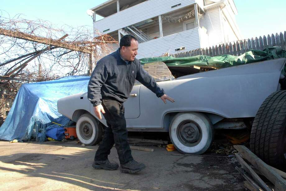 Baudilo Diaz points to the propeller under the amphibious car he's restoring  on the west side of Stamford, Conn. on Monday January 7, 2013. Photo: Dru Nadler / Stamford Advocate Freelance
