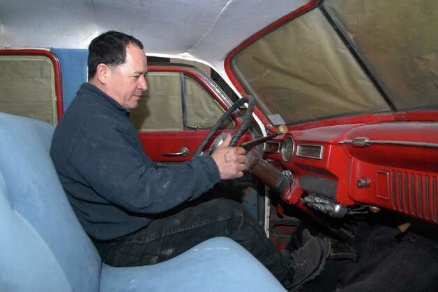Baudilo Diaz is restoring a amphibious car, a English taxi and and DeSoto which he's sitting in on the west side of Stamford, Conn. on Monday January 7, 2013. Photo: Dru Nadler / Stamford Advocate Freelance