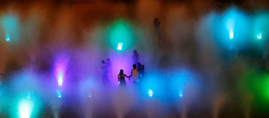 Rainbow squirts: Water spouts illuminated by colored lights shower people at the Revolution Monument in Mexico City. The once-neglected plaza with an Arc de Triumph-style monument to Mexico's 1910 revolution had become a homeless encampment before being transformed with the multi-hued fountain. Photo: Julio Cortez, Associated Press