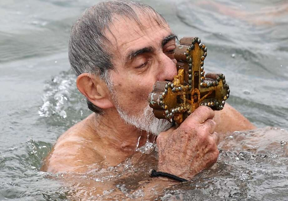 Merry Orthodox Christmas! A Greek Orthodox swimmer kisses a wooden cross he retrieved from the Bosphorus River's Golden Horn during Epiphany Day festivities at the Church of Fener Orthodox Patriarchiate in Istanbul. The Orthodox faith uses the old Julian calendar, which marks Christmas 13 days after its more widespread Gregorian calendar counterpart of Dec. 25. Photo: Bulent Kilic, AFP/Getty Images