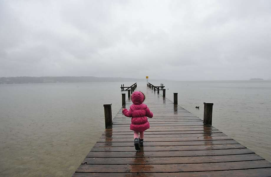 Under foreboding skies,a little girl walks on a pier at Starnberger See lake near Niederpoecking, Germany. Photo: Andreas Gebert, AFP/Getty Images