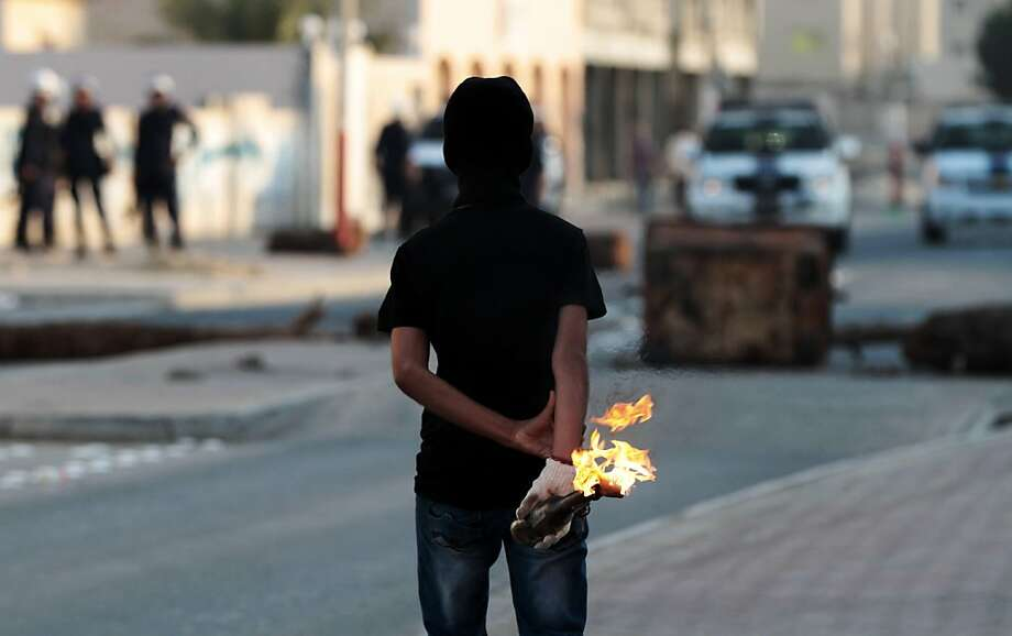 Behind my back? Why nothing, officer: An anti-government protester prepares to throw a Molotov cocktail during clashes in Malkiya, Bahrain. Photo: Hasan Jamali, Associated Press