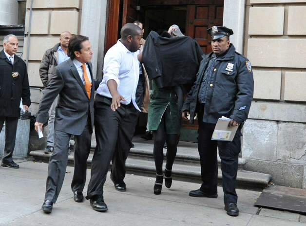 FILE - Lindsay Lohan, second from right, is escorted from the 10th Precinct police station, with her face shielded, in this Nov. 29, 2012 file photo taken in New York after being charged for allegedly striking a woman at a nightclub. Lohan is scheduled to appear in court Monday Jan. 7, 2013 to face assault charges in connection with the fight at a Manhattan nightclub. (AP Photo/ Louis Lanzano) Photo: Louis Lanzano