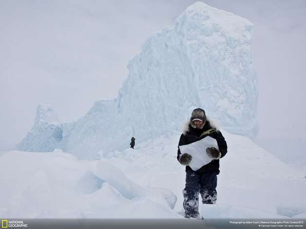 "Viewers' Choice winner in ""places"" category: ""Iceberg Hunters""Photographer: Adam CoishLocation: Pond Inlet, Nunavut, CanadaCoish: ""Chipping ice off an iceberg is a common way for the Inuit community to retrieve fresh drinking water while on the land. During a weekend long hunting trip, we came upon this majestic iceberg frozen in place. It was a perfect opportunity to grab enough ice and drinking water for the remainder of the trip."" Photo: Adam Coish / 2012 National Geographic Photography Contest"
