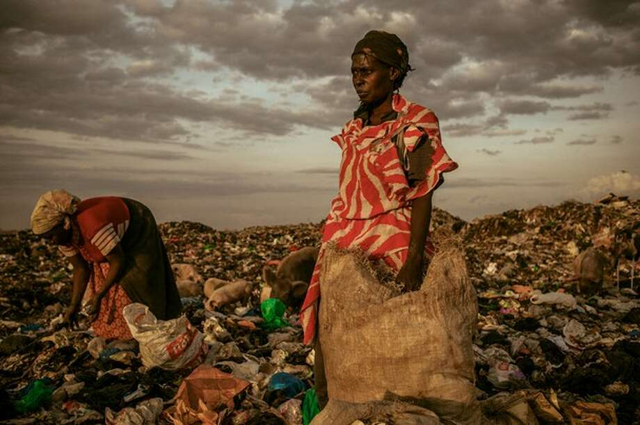 "Winner in the ""people"" category: ""Amongst the Scavengers""Photographer: Micah AlbertLocation: Dandora, Kenya Albert: ""Kenya's Dandora Municipal Dump site is the only dumping location for waste in Nairobi, East Africa's most populous city. Located just 8 km from the central business district, the 30-acre Dandora site literally spills into the households of nearly 1 million people living in nearby slums.""""Behind the statistics of children with respiratory ailments, toxic blood lead levels, skin disorders, and fatal diseases directly attributed to the waste are stories of communities that have grown to depend on the dump - from street children who live off the money they make selling food and other items they find in its piles, to residents who are paid pennies a day by private cartels to sort and recycle waste."" ""The country's leadership has long shown alarming indifference to Dandora – ignoring environmental laws, UN-commissioned health studies, and calls for closure from human rights groups. At the end of the day, women are allowed to pick through the dumpsite.""
