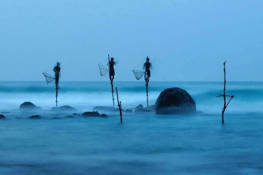 """Honorable mention: """"Stilt Fishing""""Photographer: Ulrich LambertLocation: Midigama, Sri LankaLambert: """"Stilt fishing is a typical fishing technique only seen in Sri Lanka. The fishermen sit on a cross bar called a petta tied to a vertical pole planted into the coral reef. This long exposure shot shows how unstable their position is."""" Photo:  Ulrich Lambert / 2012 National Geographic Photography Contest"""