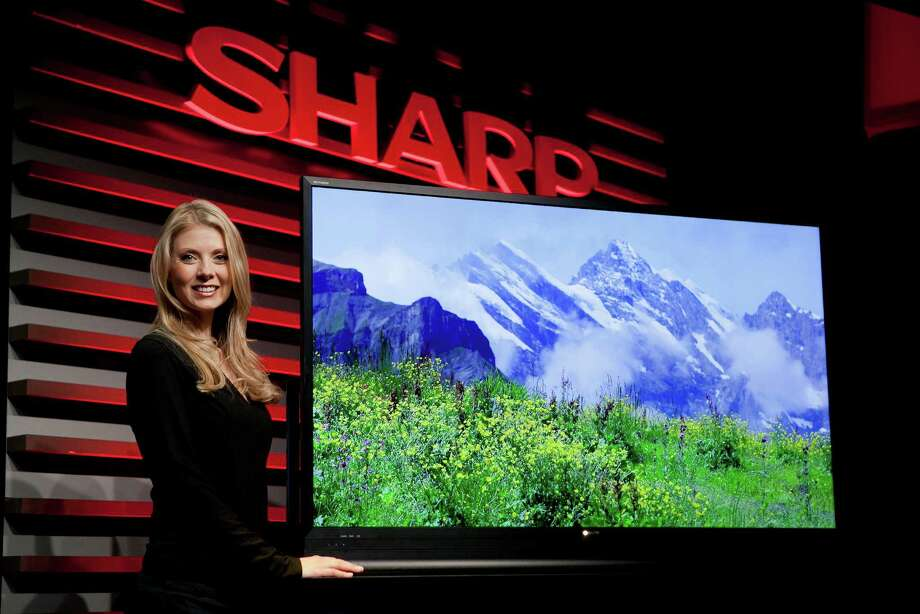 A model stands next to a Sharp Corp. 60-inch ICC Purios television during a news conference prior to the 2013 Consumer Electronics Show in Las Vegas, Nevada, U.S., on Monday. Photo: Andrew Harrer, Bloomberg / © 2013 Bloomberg Finance LP