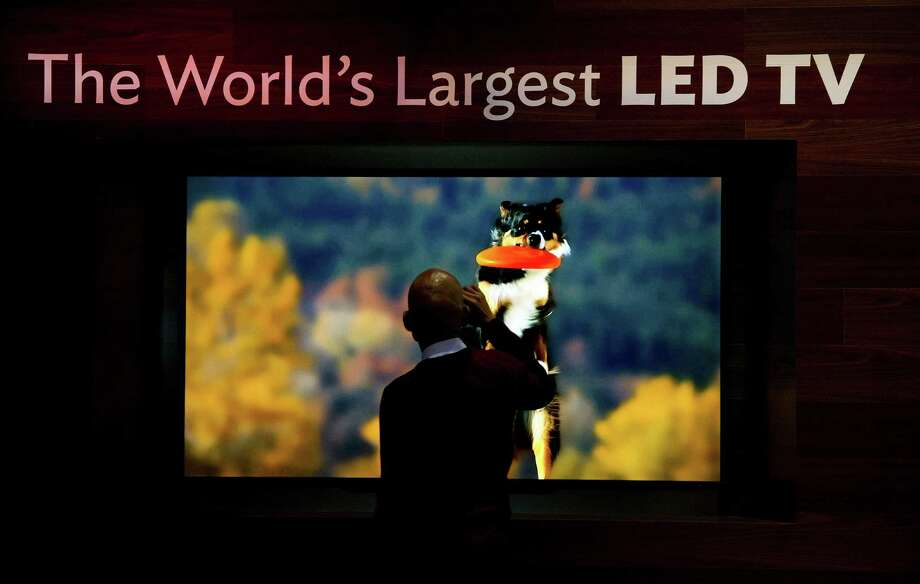A spectator stops to take a photograph of a Sharp Corp., television on display prior to the 2013 Consumer Electronic Show in Las Vegas, Nevada, U.S., on Monday. Photo: David Paul Morris, Bloomberg / © 2013 Bloomberg Finance LP