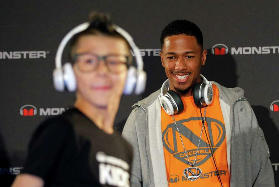 Recording artist Nick Cannon looks at a model wearing a new headphone by Monster on Monday. Photo: Jae C. Hong, Associated Press / AP