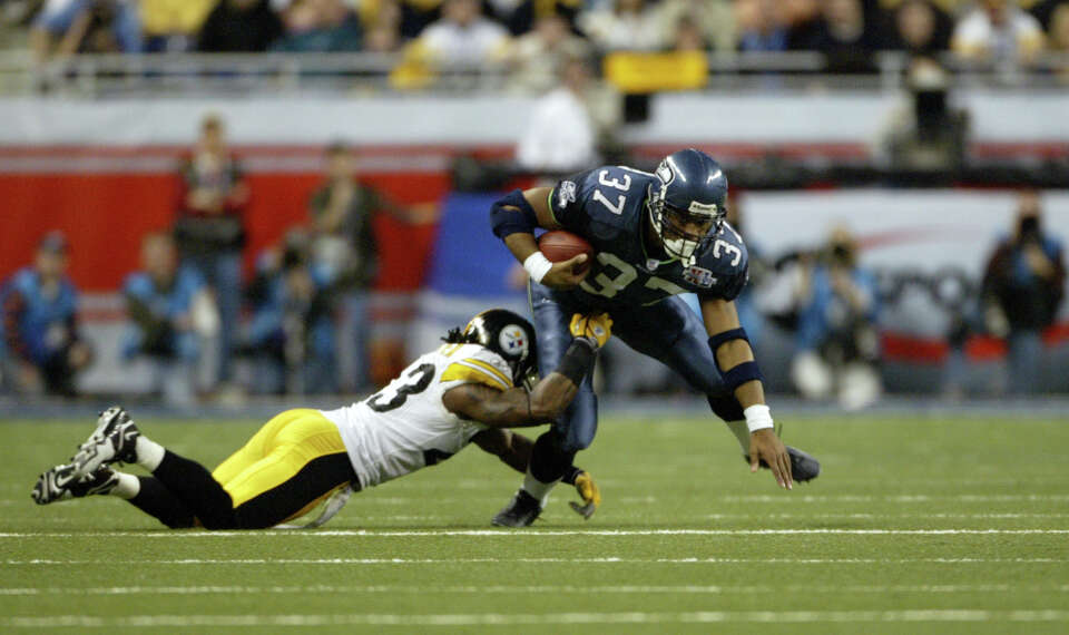 Shaun Alexander tries to escape the tackle of Tyrone Carter.