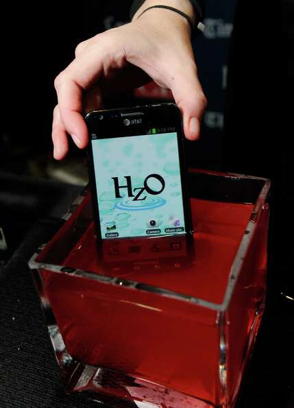 An iPhone using HzO Waterblock technology is displayed in a bowl of water during a press event at th