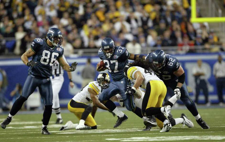 Shaun Alexander carries the ball as Jerramy Stevens looks on.