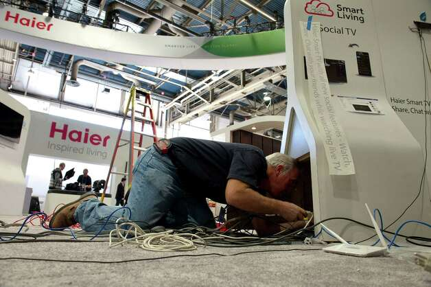 An electrician installs cables at the Haier Inc. booth prior to the 2013 Consumer Electronic Show in Las Vegas, Nevada, U.S., on Monday, Jan. 7, 2013. The 2013 CES trade show, which runs until Jan. 11, is the world's largest annual innovation event that offers an array of entrepreneur focused exhibits, events and conference sessions for technology entrepreneurs. Photographer: David Paul Morris/Bloomberg Photo: David Paul Morris, Bloomberg / © 2013 Bloomberg Finance LP