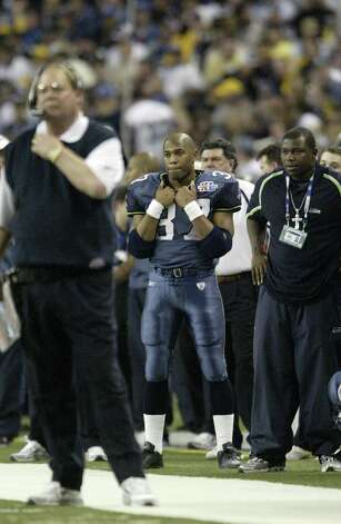 Shaun Alexander follows the action on the field behind head coach Mike Holmgren. Photo: Mike Urban/seattlepi.com/MOHAI / Seattle Post-Intelligencer