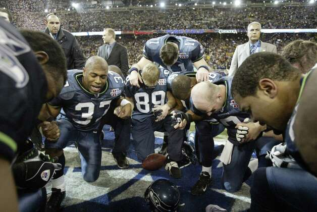 Players kneel at the center of the field for a post-game prayer. Photo: Mike Urban/seattlepi.com/MOHAI / Seattle Post-Intelligencer