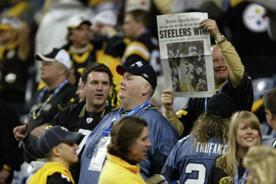A Steelers fan celebrates with the traditional, quickly prepared front page of a newspaper. Photo: Dan DeLong/seattlepi.com/MOHAI