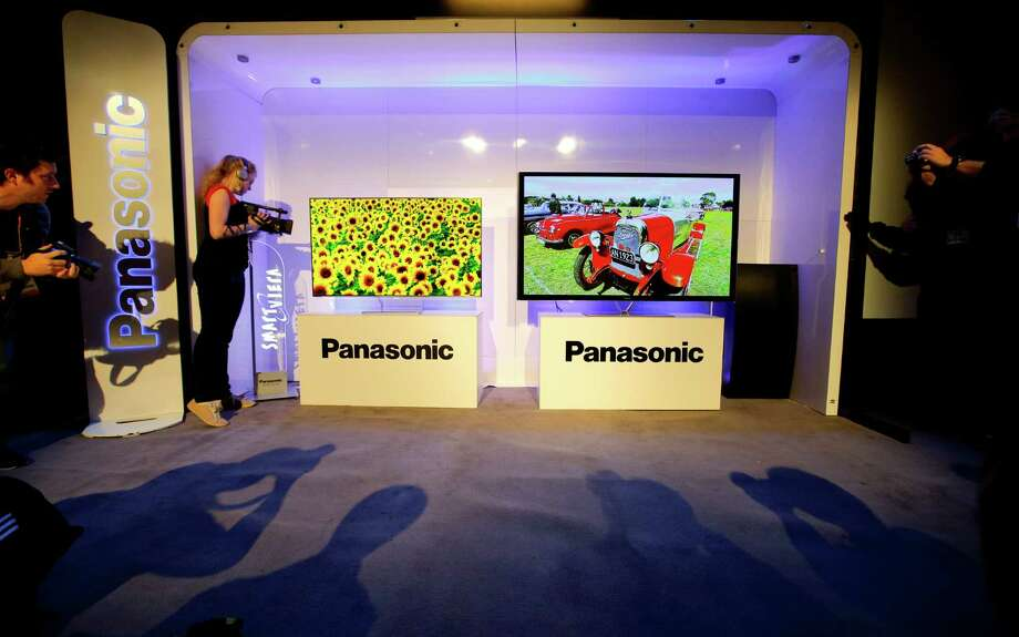 Show attendees photograph Panasonic's new televisions during a news conference at the International Consumer Electronics Show in Las Vegas, Monday, Jan. 7, 2013. The 2013 International CES gadget show, the biggest trade show in the Americas, is taking place in Las Vegas this week. (AP Photo/Jae C. Hong) Photo: Jae C. Hong, Associated Press / AP