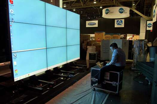 Sharp Electronics employee Michael Nenortas programs a flat screen display at the company's booth for the International Consumer Electronics Show, Sunday, Jan. 6, 2013, in Las Vegas. The show, which drew more than 3,100 exhibitors in 2012 and is open only to industry affiliates, begins Tuesday and runs through Friday. (AP Photo/Julie Jacobson) Photo: Julie Jacobson, Associated Press / AP