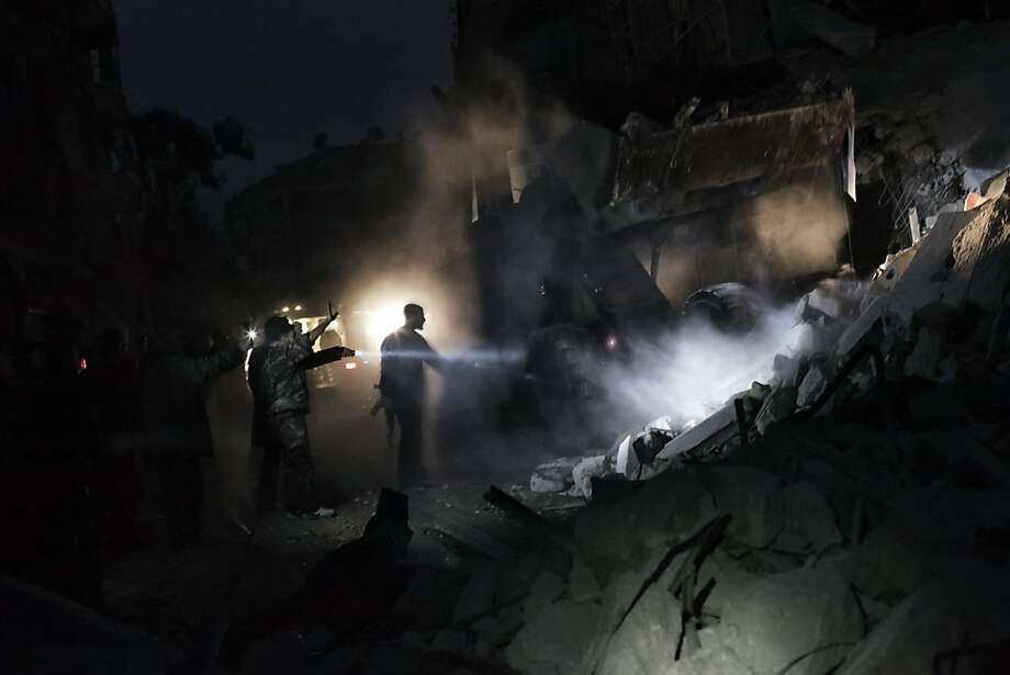 Searchers look for survivors in the rubble of a building hit by a missile in Aleppo, Syria. The country's former commercial hub has been a major front in the civil war since July. Photo: --, AFP/Getty Images