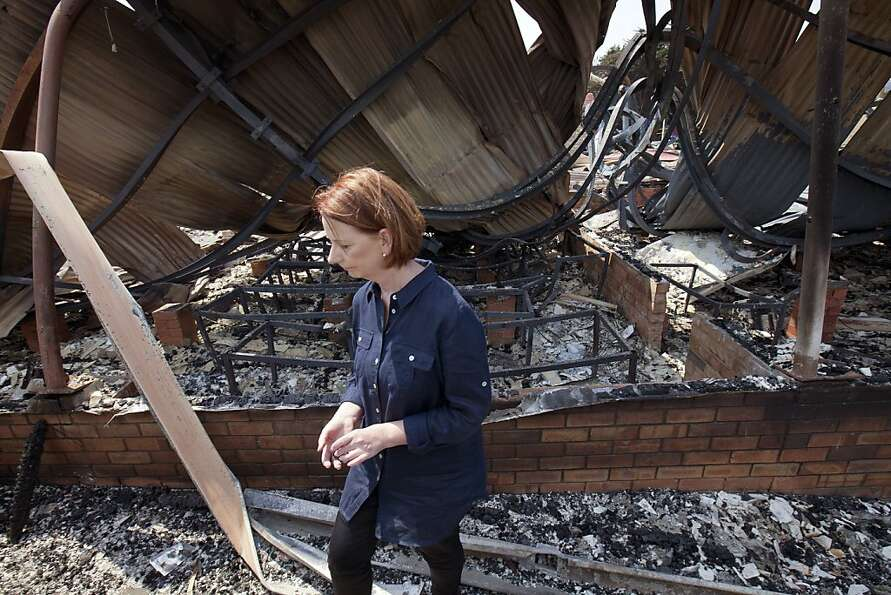 Australian Prime Minister Julia Gillard inspects the burnt remains of the Dunally school in southeas