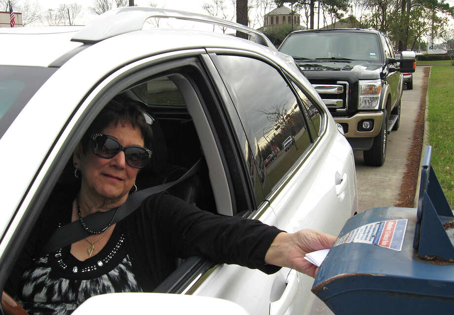 Barbara Mattison stuffs mail into an overworked mailbox at the Tobe Hahn post office drive-through Monday on Dowlen Road. The U.S. Postal Service recently removed three other boxes in preparation to install a single, larger box. Similar changes are taking place at the South End post office on Avenue A and at the Walden Road post office.  Dan Wallach/The Enterprise