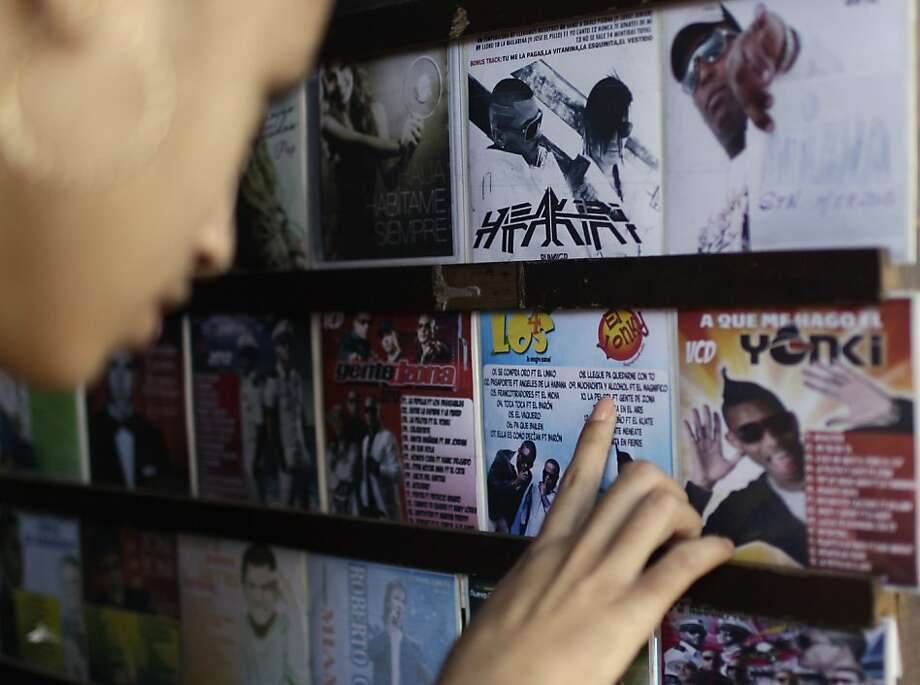 Yadisbel Ruiz, 17, checks out a reggaeton album at a music and movie store run from a home in Havana. Photo: Franklin Reyes, Associated Press