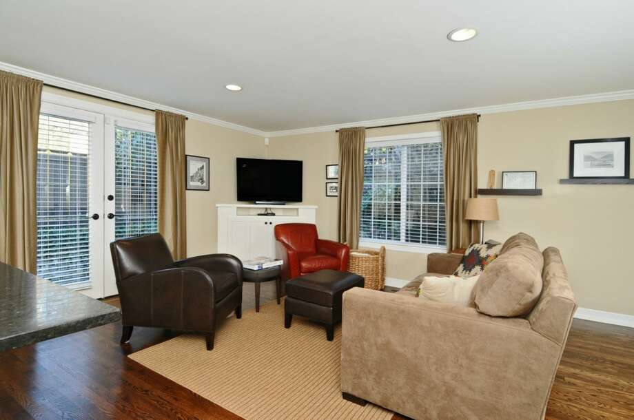 Family room of 5916 37th Ave. S.W. The 2,860-square-foot Cape Cod-style house, built in 1944, has four bedrooms, 1.75 bathrooms, an updated kitchen, a rec room and a patio on a 6,400-square-foot lot. It's listed for $539,000, although a sale is pending. Photo: Courtesy Leslie Fox/Windermere Real Estate
