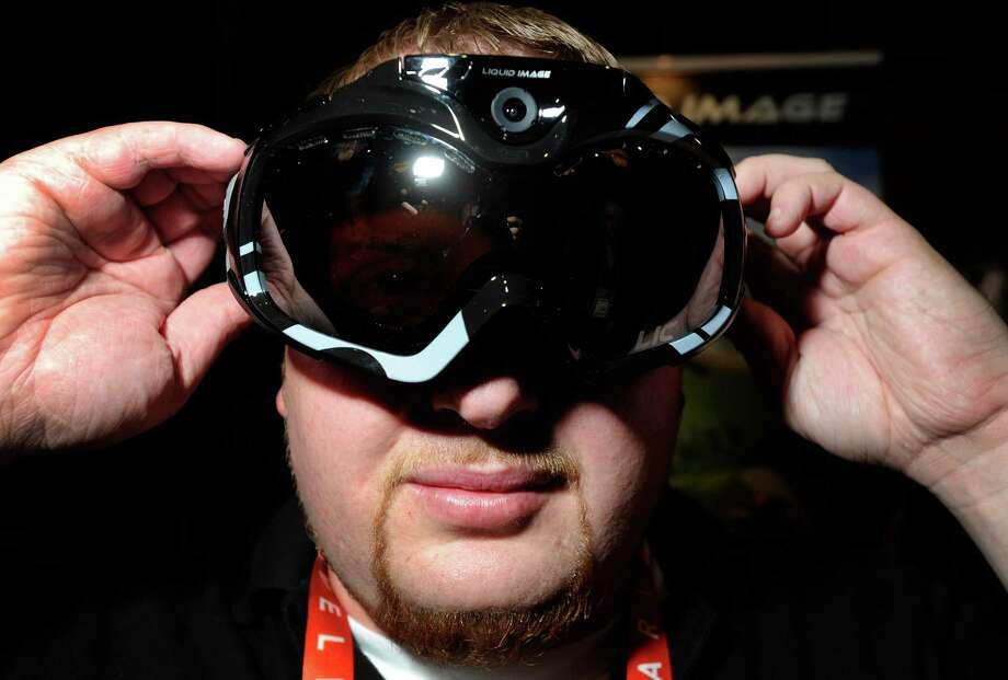 John Noonan displays a pair of Liquid Image goggles with a built-in camera at a press event for the 2013 International Consumer Electronics Show in Las Vegas, Nevada. CES, the world's largest annual consumer technology trade show, runs from January 8-11 and is expected to feature 3,100 exhibitors showing off their latest products and services to about 150,000 attendees. Photo: David Becker, Getty Images / 2013 Getty Images