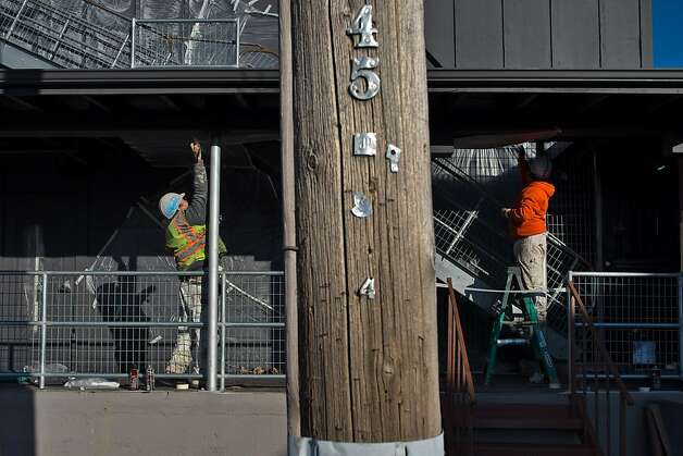 Workers mask off portions of an old cannery for painting at the site now known as the Barlow. Photo: Alvin Jornada, Special To The Chronicle