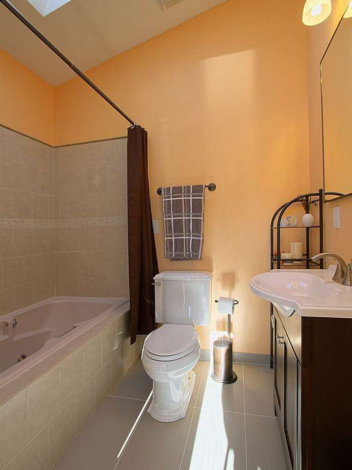 Bathroom of 5205 25th Ave. S.W. The 2,250-square-foot house, built in 2010, has five bedrooms and 3.75 bathrooms -- including a mother-in-law apartment -- heated floors, skylights, a basement bonus room, balconies and a front porch. It's listed for $530,000. Photo: Courtesy Elena Micheva/Keller Williams Realty