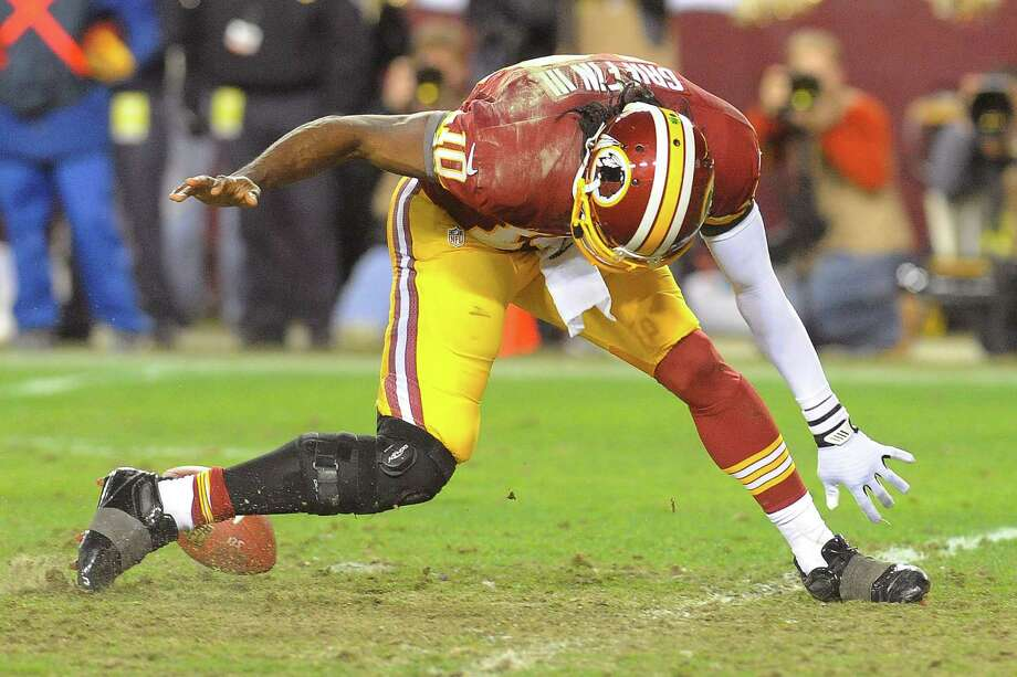 Washington Redskins quarterback Robert Griffin III twists his knee chasing a loose ball during the second half of an NFL wild card playoff football game against the Seattle Seahawks in Landover, Md., Sunday, Jan. 6, 2013. (AP Photo/Richard Lipski) Photo: Richard Lipski, Associated Press / FR170623 AP
