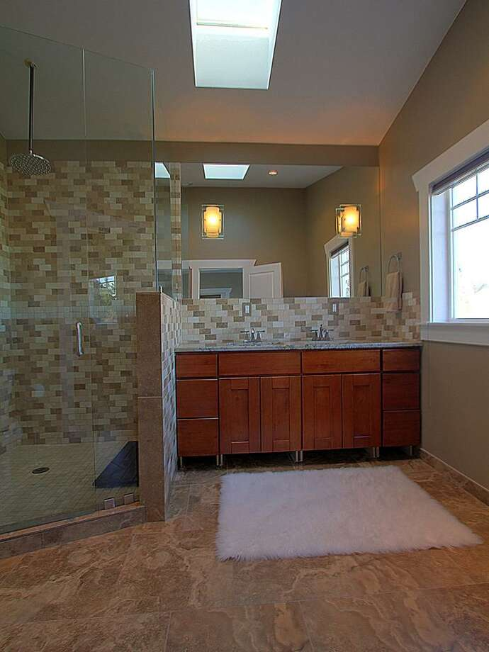 Three-quarter bathroom of 5205 25th Ave. S.W. The 2,250-square-foot house, built in 2010, has five bedrooms and 3.75 bathrooms -- including a mother-in-law apartment -- heated floors, skylights, a basement bonus room, balconies and a front porch. It's listed for $530,000. Photo: Courtesy Elena Micheva/Keller Williams Realty