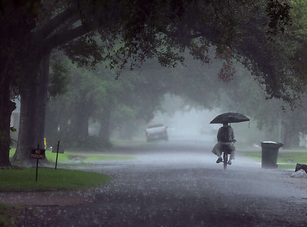 Using an umbrella a man rides his bike through a north Beaumont neighborhood on Thursday. Heavy rains triggered accidents, flash flood warnings and complications for Southeast Texas travelers.  Photo taken Thursday, July 12, 2012 Guiseppe Barranco/The Enterprise Photo: Guiseppe Barranco, STAFF PHOTOGRAPHER / The Beaumont Enterprise