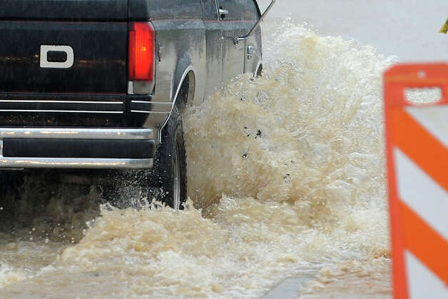 A truck sprays water while driving on the U.S. 69 feeder road Thursday. Heavy rains triggered several accidents, flash flood warnings and complications for Southeast Texas travelers.  Photo taken Thursday, July 12, 2012 Guiseppe Barranco/The Enterprise Photo: Guiseppe Barranco, STAFF PHOTOGRAPHER / The Beaumont Enterprise