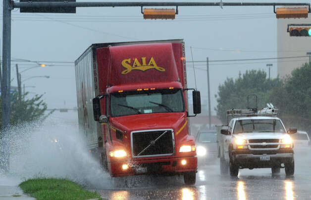 A truck sprays water while driving College Street feeder road Thursday. Heavy rains triggered several accidents, flash flood warnings and complications for Southeast Texas travelers.  Photo taken Thursday, July 12, 2012 Guiseppe Barranco/The Enterprise Photo: Guiseppe Barranco, STAFF PHOTOGRAPHER / The Beaumont Enterprise