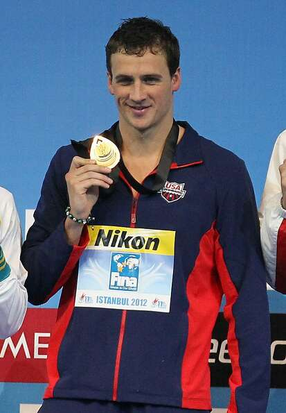 Gold medalist Ryan Lochte of U.S. poses for the photographers during men's 100 meters individual med