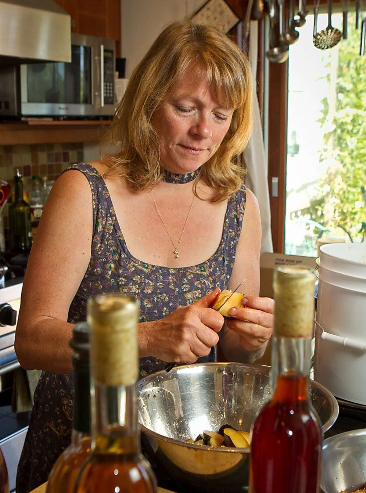 MaryEllen Kirkpatrick cuts up plums for making Plum Melomel at her home in San Francisco, Calif., on Tuesday, July 31st, 2012. She is making Plum Melomel from fermented honey and plums.