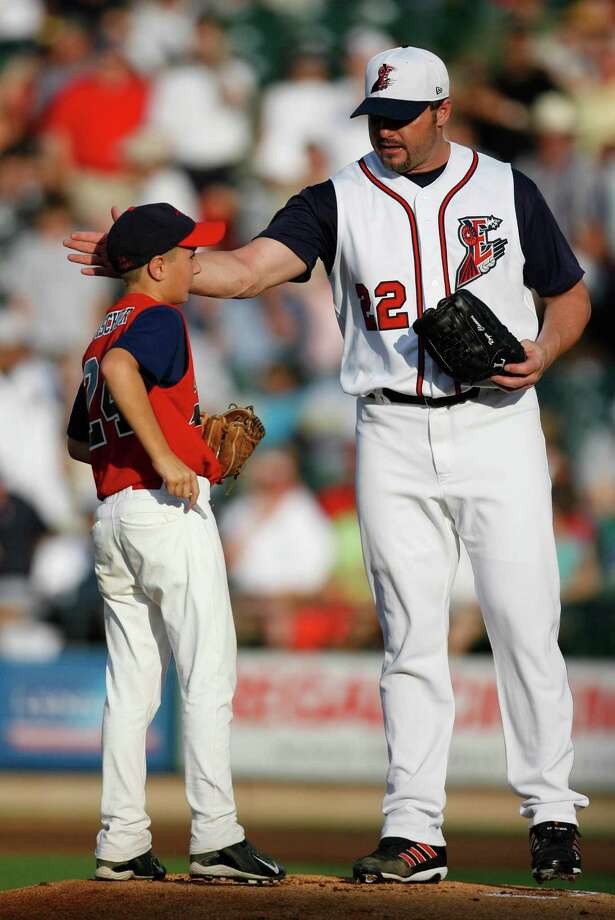 Roger Clemens stands on the mound with Logan Fischer, 10, one of the baseball buddies from the Round Rock Select Cougar team during the National Anthem before the Round Rock Express-New Orleans Zephyrs minor league game at Dell Diamond in Round Rock on June 16, 2006.  Roger Clemens started the game in preparation for his return to the Astros. Photo: KAREN WARREN, Houston Chronicle / Houston Chronicle