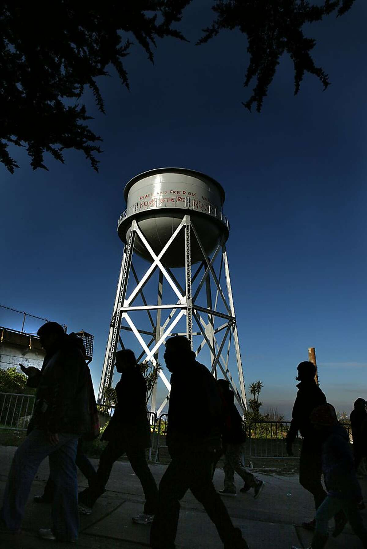 Tourists passing the restored water tank on Alcatraz in San Francisco, California, on Thursday, January 3, 2013. The National Park service has restored the grafitti the American Indians had placed on the landmark water tank on Alcatraz during their occupation in the sixties.