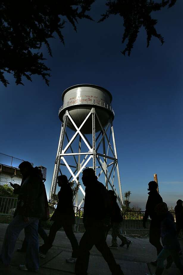 Tourists passing the restored water tank on Alcatraz in San Francisco, California, on Thursday,  January 3, 2013.   The National Park service has restored the grafitti the American Indians had placed on the landmark water tank on Alcatraz during their occupation in the sixties. Photo: Liz Hafalia, The Chronicle
