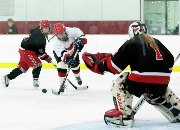 Greenwich high school's Emily Bacon take a shot on New Canaan high school goalie Nathalie Deney in a girls ice hockey game played at the Dorothy Hamill Skating Rink, Greenwich, CT on Monday January 7th, 2013. Photo: Mark Conrad / Stamford Advocate Freelance